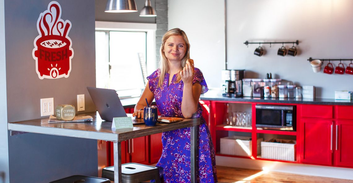 wide shot of Ashley Neighbor standing at the counter with her laptop smiling at the camera