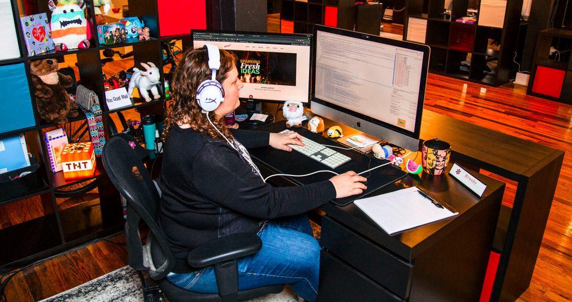 wide shot of Brooke Ruckdaschel sitting at her desk reviewing front end web design with headphones on