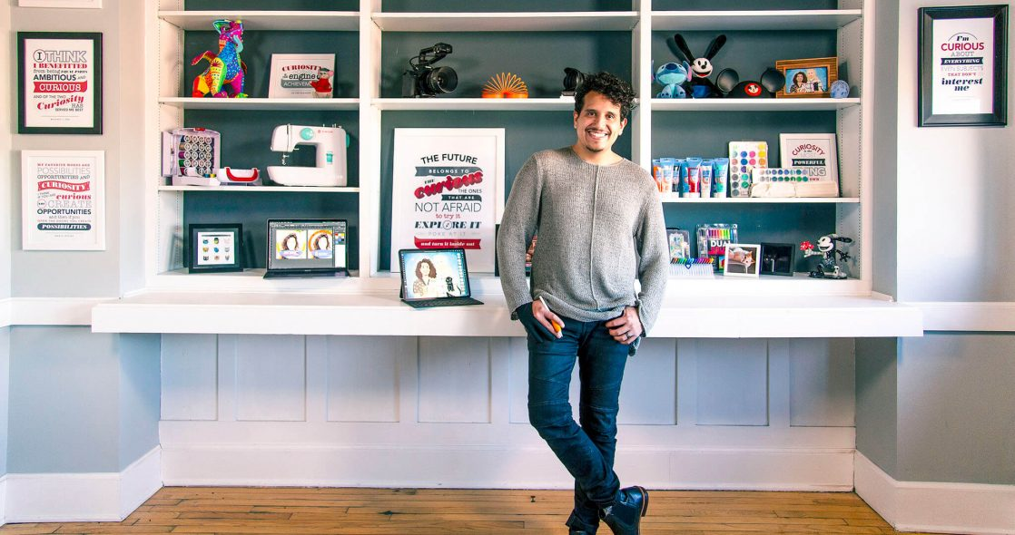 wide shot of Jav Ducker standing in front of shelves with a digital sketch pad and items that represent him on the shelves behind him