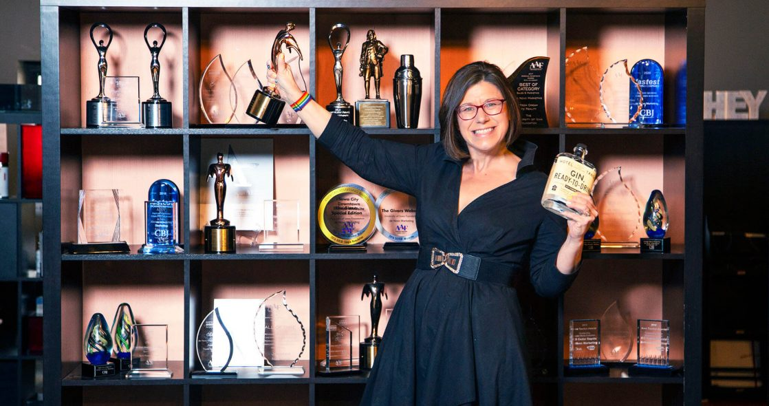 wide shot of Jen Neumann standing in front of a shelf with rewards on it and holding a bottle of gin