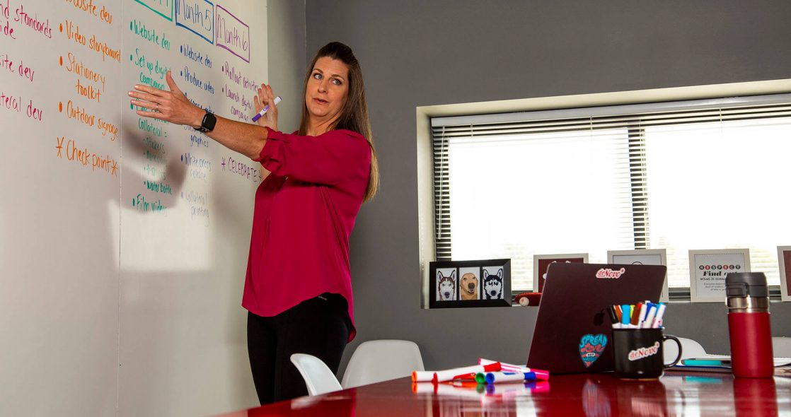 wide shot of Jennifer Shaddox standing next to a whiteboard with a 6 month marketing strategy