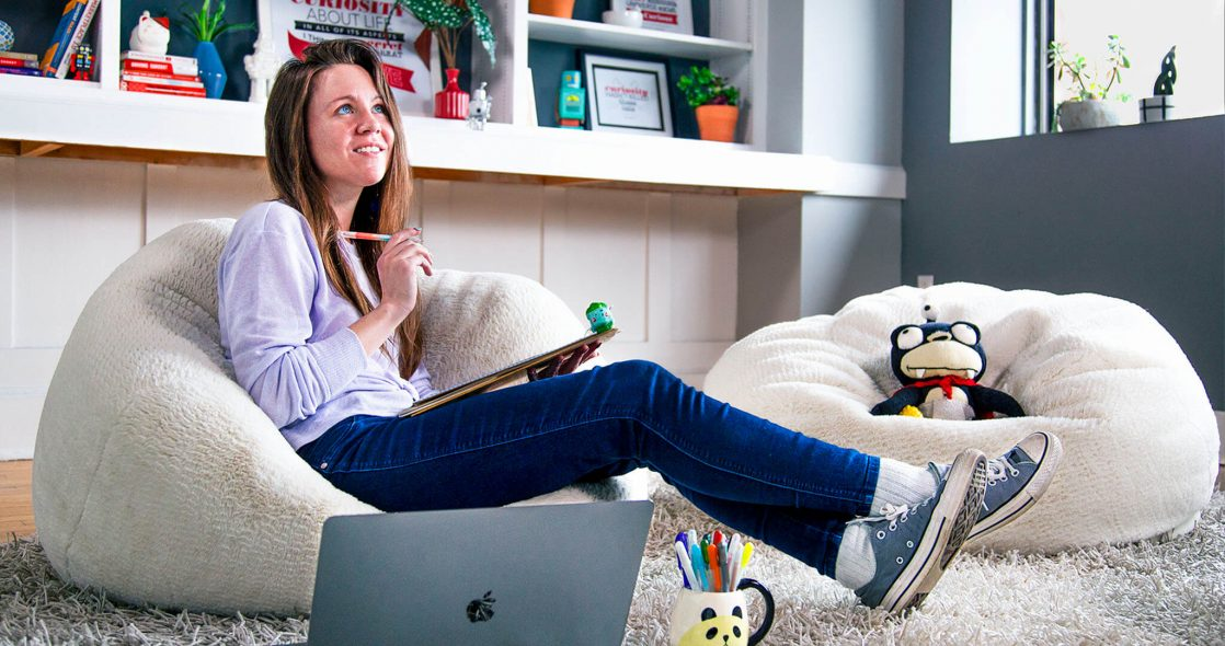 wide shot of Kelly Stapella sitting in a beanbag with a pen in her hand and a notepad in her lap