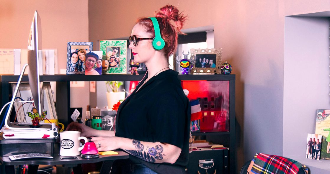 wide shot of Lydia Sax working at her standing desk with brightly colored headphones on